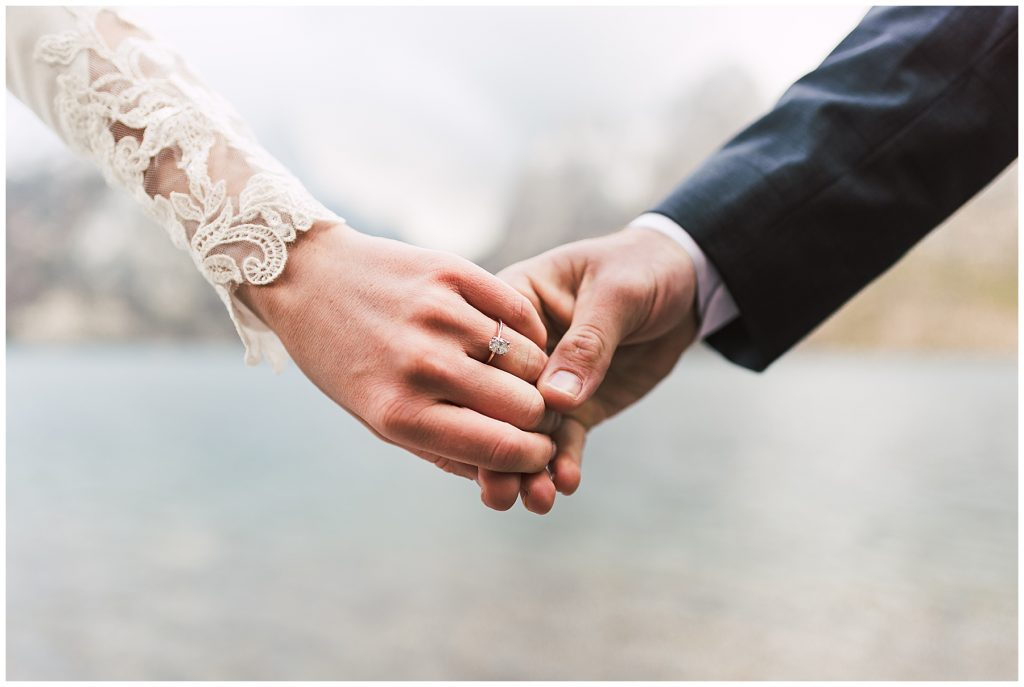 Holding hands, showing engagement ring at The Grand Teton National Park