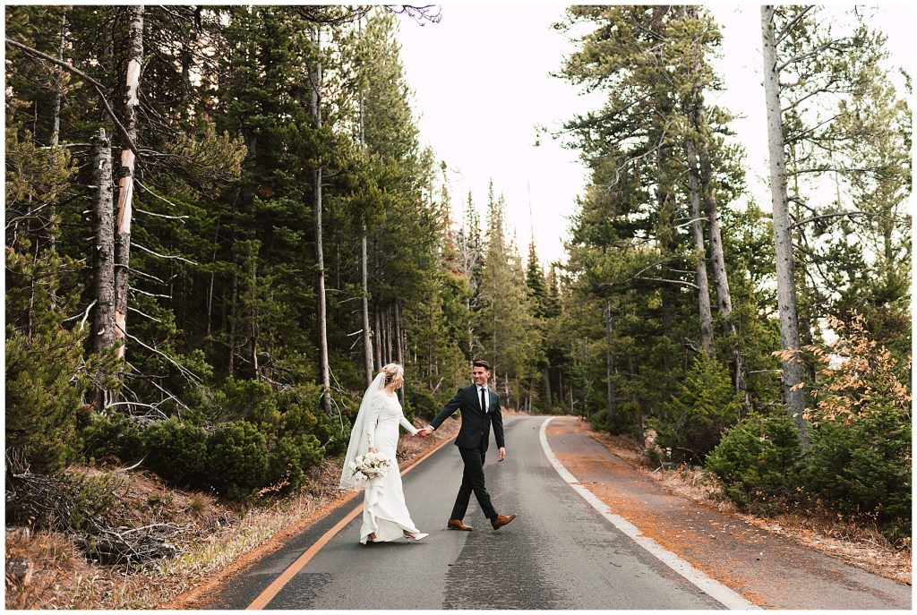 couple in wedding attire walking across road together