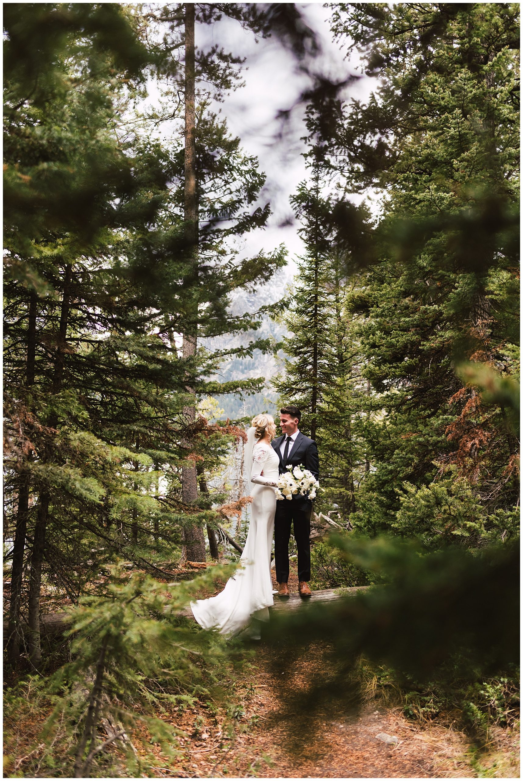 Utah Wedding Photographer captures a couple in wedding attire, framed by pine trees